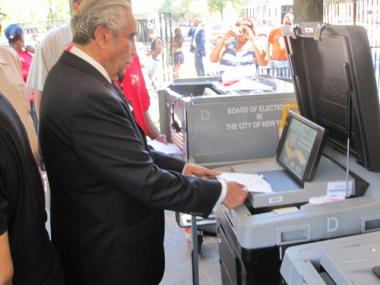 Rep. Charlie Rangel slides his ballot into the optical scanner during a demonstration.