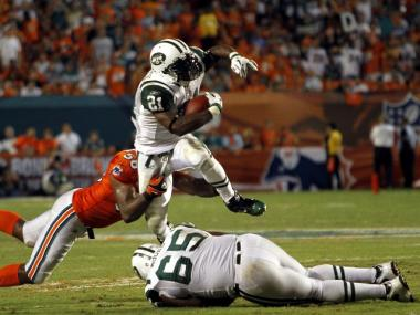 LaDainian Tomlinson breaks a tackle while the Jets played the Dolphins in Miami Sunday.