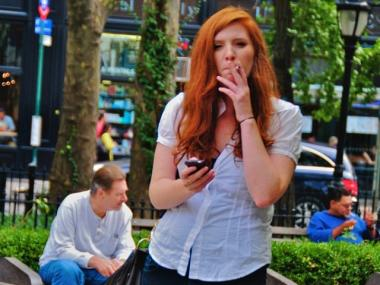 A woman smokes in Lincoln Square in 2008. Smoking in city parks and beaches would be banned under a new proposal expected to be announced Monday.