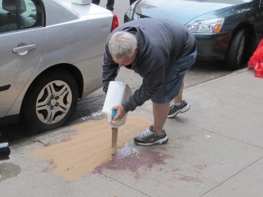 Someone tries to clean the blood in front of 272 E. Seventh St.