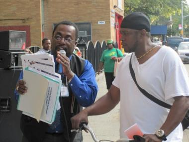 Rev. Williams hands out job applications after a spate of violence in August.