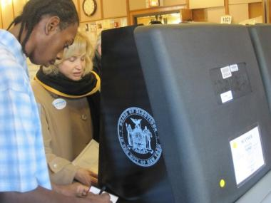Poll worker Kenneth Morris, 25, helps Congresswoman Carolyn Maloney re-scan her ballot after her first few tries didn't take Tuesday.