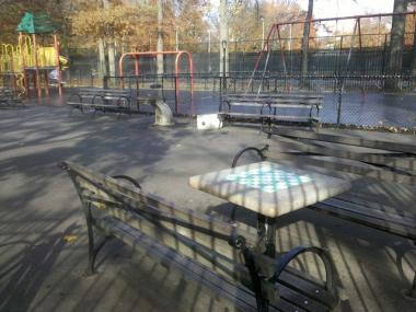 The chess tables at Inwood Hill Park overlook the playground.