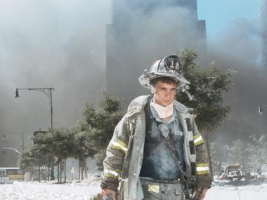 An unidentified firefighter standing near Ground Zero on 9/11, surrounded by dust and ash.
