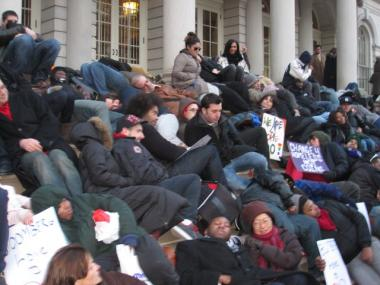 LGBT youth and advocates laid down on the steps of City Hall to protest a prior round of cuts (since restored) last December.