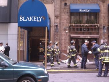 Firefighters gather hoses after putting out a fire at the Blakely hotel in Midtown on March 30, 2011.