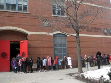 Children lined up outside P.S. 234 on the way to class recently. P.S. 234 could not fit all the kindergarteners who applied this year so 22 families will have to go to P.S. 130 in Chinatown instead.