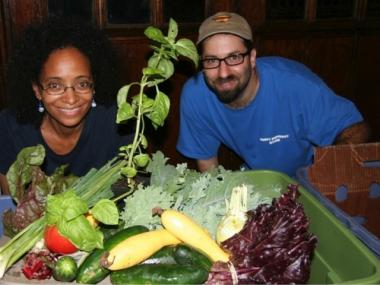 West Harlem CSA newsletter editor Arminda Thomas and Josh Feinberg pose with a box of produce from Windflower Farm.