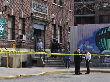 People look on as police investigate a shooting outside the J. Rozier Hansborough Recreation Center on Monday, April 11, 2011.