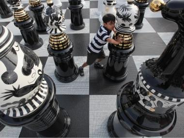 A boy moves a giant chess piece on a board in London's Trafalgar Square.
