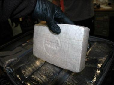 Investigator holding a brick of cocaine seized in the bust.