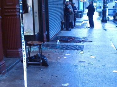 Broken glass is scattered along the sidewalk on Orchard Street outside Pilgrim store.