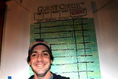 Kevin Fair stands in front of a painting he made to mimic the guest checks that he doodles on as a waiter at Miller's Pub.