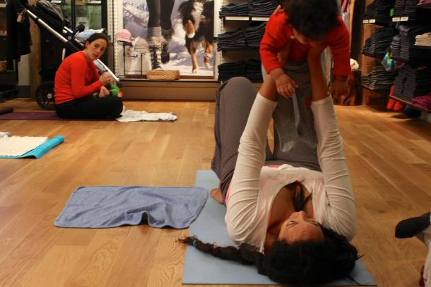 At 9 a.m. on Friday morning, neighborhood moms and babies hit the mat together at Athleta apparel store for a free interactive yoga class.