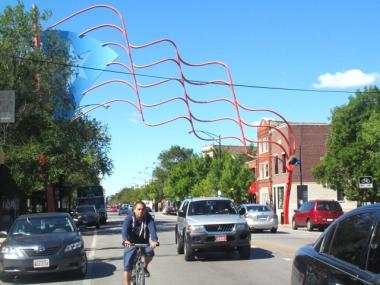 A sculpture of the Puerto Rican flag hangs over a stretch of Divison Street, the Humboldt Park neighborhood's El Paseo Boricua.