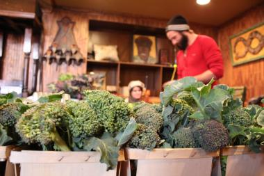Vendors with broccoli at the indoor Pilsen Community Market.
