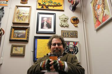 Brian Posen, founder of Chicago's SketchFest, sits in his Stage 773 office, which is deliberately decorated with tacky art.
