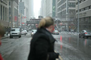 "A woman walks in front of the ""L"" on Wacker Drive during a winter snowstorm."