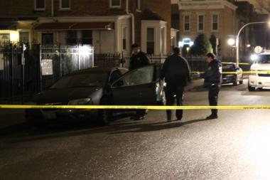 Police investigate a car near where Gavin Williams, 28, was shot and killed early Sunday morning