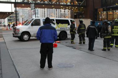 The driver of the Aries Shuttle that caused a Hazmat fuel spill looks on as fire crews contain the leak at 77 E. Wacker Drive on Tuesday.