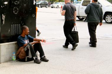 A man panhandles on Michigan Avenue earlier this year. The city's Department of Family and Support Services is seeking volunteers for a tallying of Chicago's homeless population next month.