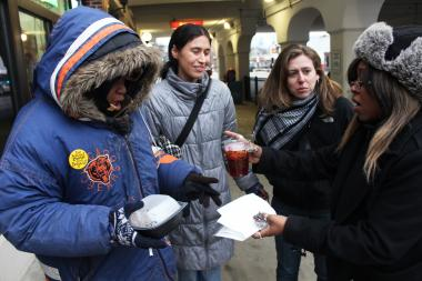 Tish Morris, 29, (r.) hands homeless woman Jennifer Green (l.) food and a drink on Morse Avenue on Christmas Eve. Others, including Occupy Rogers Park members Kelly Hayes (to Green's right) and Lindsay Herer, are helping Green find permanent housing.