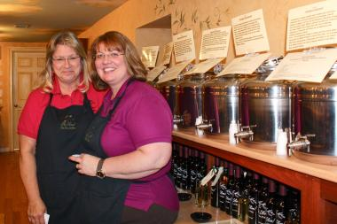 Sandy Schuenemann, left, and Mary Koval use their teaching backgrounds to educate customers of the approximately 30 olive oils and vinegars on tap.
