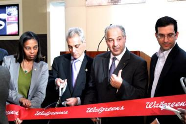 Standing next to store manager Lisa McMiller (left), Mayor Rahm Emanuel prepares to cuts a ribbon during a grand opening ceremony Dec. 4 at a new Walgreens at 1601 N. Milwaukee Ave. Ald. Scott Waguespack (32nd) is at right.  The store opened Nov. 21.