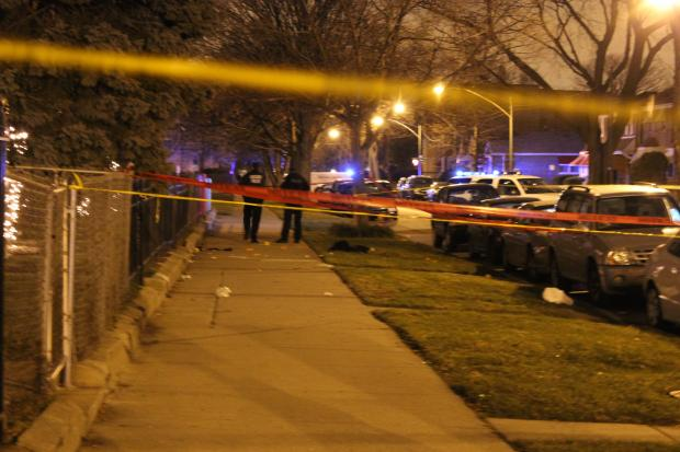 Police survey the scene where four men, ages 15 to 22, were shot late Monday.