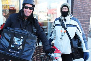 "Craig Gernhardt (left) and another bicycler delivery guy who only wanted to go by ""Rider X,"" deliver food for a few Rogers Park eateries — no matter the temperature."