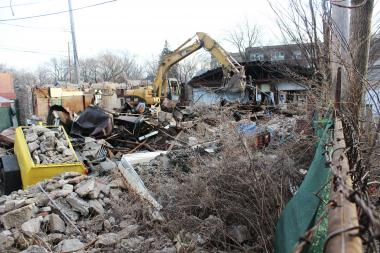 A tractor tears down the building at 7312-13 N. Damen Ave. after a judge ordered its demolition due to unsafe conditions.