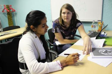 Blair Brettschneider, who founded GirlForward in 2011, helps Khina with vocabulary words before she starts classes a Truman College.