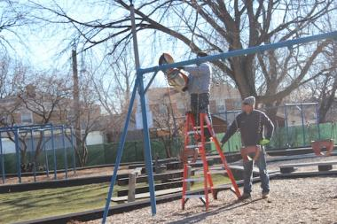 Workers dismantle a swing set Wednesday at Merrimac Park.