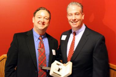 Garrett FitzGerald (left), executive director of the Northcenter Chamber of Commerce, presented outgoing Simon Stein with a watch to commemorate his service to NCC.