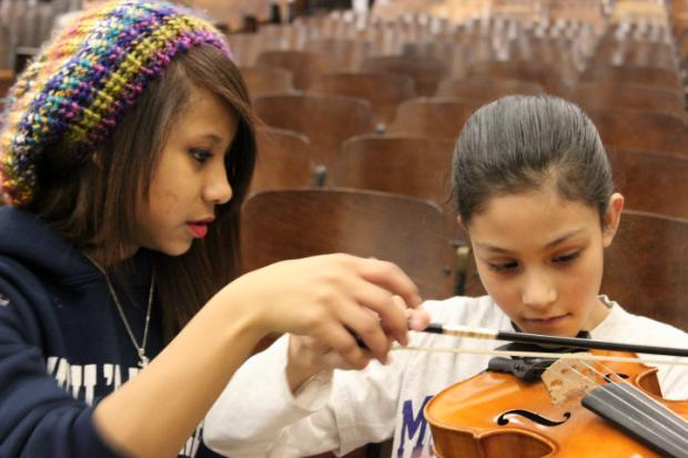 Students from Amundsen H.S.'s orchestra give music lessons to fourth- and fifth-graders at McPherson Elementary.