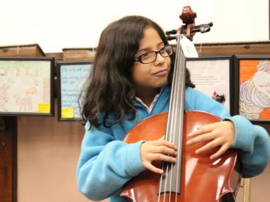 A student at McPherson Elementary practices her upright bass moves during a music lesson with orchestra members from Amundsen High School.