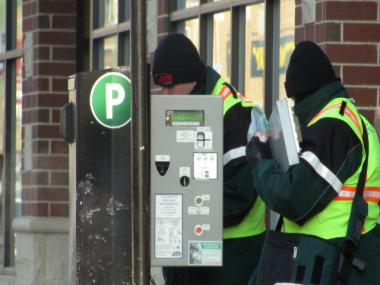 A pair of workers increase the rate at a parking meter pay box on North Clark Street near Wrigley Field in 2011.