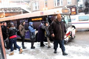 Commuters exit and prepare to board the CTA's No. 50 bus.