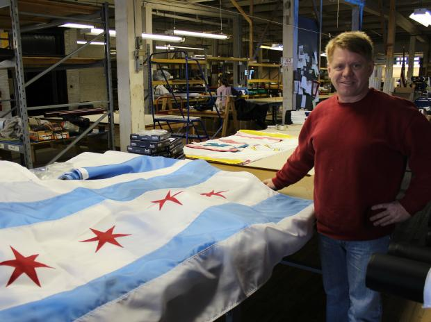 An Ashland Avenue flag manufacturer is putting the pieces back together after a massive fire at a nearby building destroyed its inventory.
