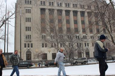 People trudge through the snow Tuesday afternoon near Chicago's criminal courthouse at 26th Street and California Avenue.