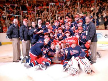 The St. Rita hockey team poses for a photo after winning the 2012 state championship at the United Center. Coach Craig Ferguson, standing far right, has led the school to two of the last three state titles.