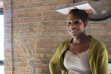 Akilah Easter of EtiquetteFemme balances a book atop her head, an exercise that promotes good posture.