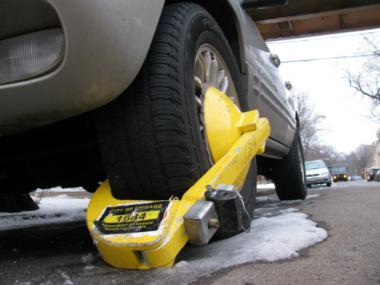 A car in Bucktown sports a bright yellow boot due to unpaid parking or red light camera tickets.