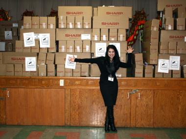 Phyllis Cavallone, St. Therese Chinese Catholic School, poses with a shipment of calculators donated by Sharp.