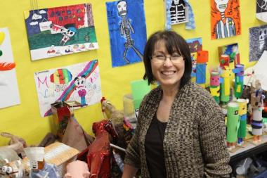 Hamilton Elementary multicultural studies art teacher Esther Pullman smiles in front of a gallery of student work.