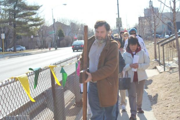 More than two dozen people marked Good Friday by walking the Stations of the Cross through Norwood Park.