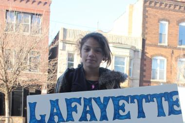 Sixth-grader Tatiana Lebron, 12, carries her viola from music practice at a rally for Lafayette in March 2013.