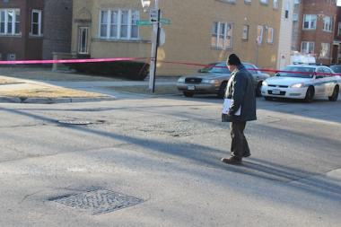 A Chicago police detective examines the scene of a shooting at Lavernge and Sunnyside avenues in Jefferson Park.
