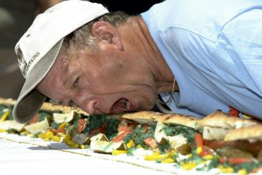 A Vienna Beef employee prepares to bite into a 37-foot-long hot dog at Chicago's Taste of Chicago on July 1, 2004.