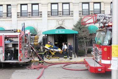 Paramedics wheel out an empty gurney at The Versailles apartment building at 5254 S. Dorchester Ave. The eighth floor caught fire after a motor overheated, but firefighters were able to contain the fire before anyone was injured.